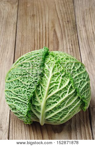 Fresh savoy cabbage on a wooden table