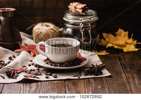 Autumn Leaves with Cup of Coffee. Ingredients Spices and Some Kitchenware on dark wooden surface.
