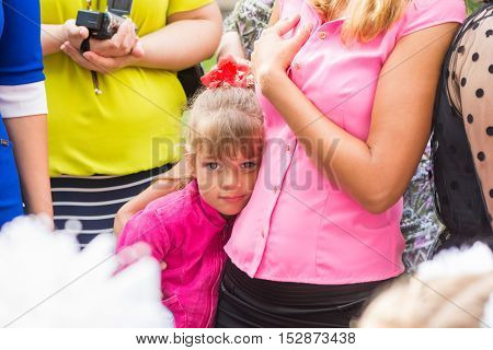 Five-year girl standing in the crowd and clung to her mother