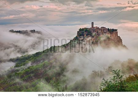 Civita di Bagnoregio, Viterbo, Lazio: picturesque landscape at dawn of the ancient village shrouded in fog on the steep tuff hill