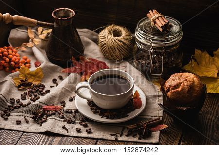 Autumn Leaves with Cup of Coffee and Muffin Ingredients Spices and Some Kitchenware on tablecloth.