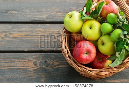 colorful and various kinds of apples in the basket on wooden background