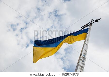 national Ukrainian flag as symbol yellow and blue color windy day outdoor on cloudy blue sky background