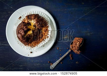Freshly baked chocolate muffin with lemon kurd inside, on a dark blue wooden table. Top view, muffin broken down spoon, cream flowed from it. Copy space