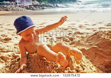 adorable toddler fell while playing in the sand