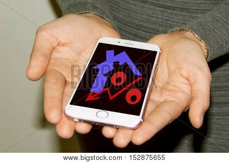 Red percentage sign and house on your phone screen . The concept of online sales of real estate .