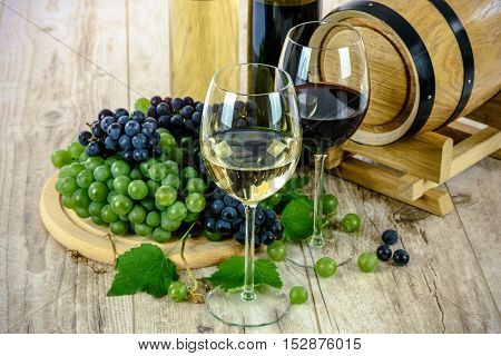 Two types of grape wine and wooden barrel on a wooden vintage table