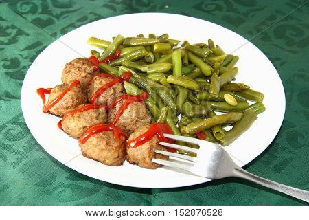 Swedish meatballs with green beans on table