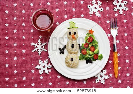 Christmas lunch with healthy kid's food in the form of a snowman and Christmas tree.