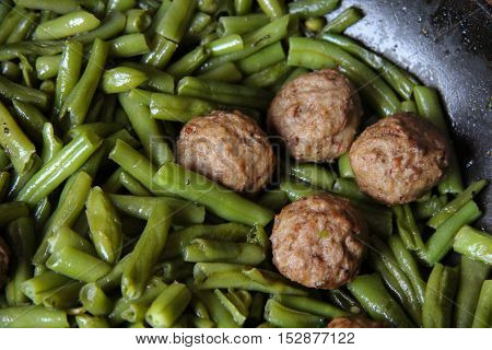Swedish meatballs with green beans in a skillet on wood