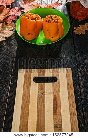 Orange paprika stuffed with vegetables and carved as halloween lanterns on the wood table decorated with maple leaves