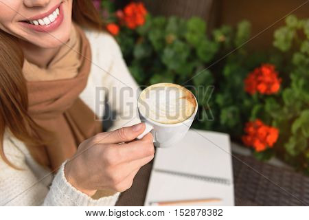 Cute young girl is enjoying hot coffee in cafeteria outdoors. She is sitting near flowers and smiling