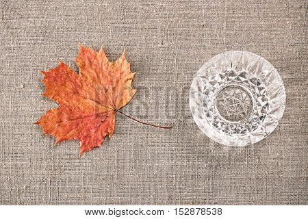 Still life with crystal bowl and fallen maple leaf. Flat lay