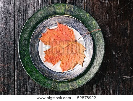 Flat lay of plates with fallen leaves on the dark wood table
