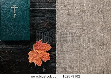 Closed holy bible and maple leaf on the dark wood table. Flat lay