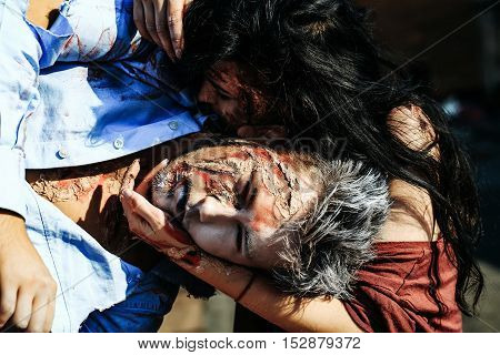 Halloween zombie couple of bloody young woman girl holds handsome man vampire or war soldier with wounds and red blood outdoors on sunny day