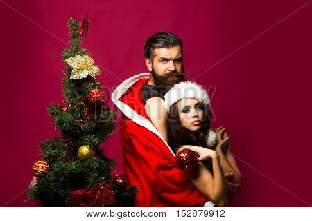 bearded santa claus man with long beard in new year coat with pretty sexy naked girl or woman in hat near decorated Christmas tree on pink background copy space