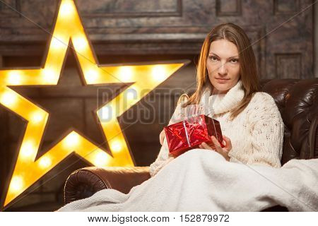 holidays, celebration and people concept - smiling woman red gift box over christmas lights background.