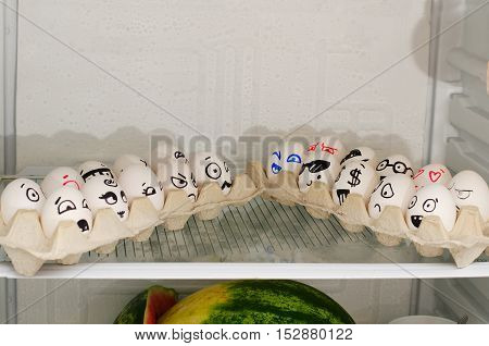 Two trays of eggs with smiles facing each other on a shelf in the refrigerator