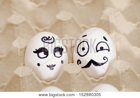 Two eggs with painted faces a lady and a gentleman