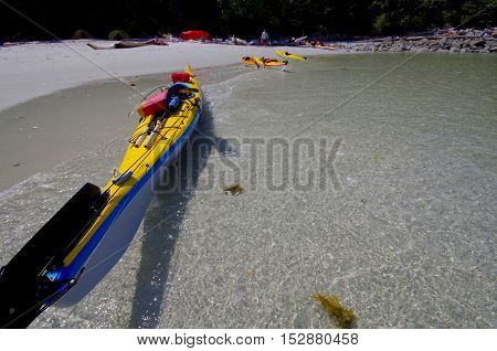 ayaks floating near the bright sand on the beautiful McMullin Group of islands in the central coast of British Columbia.