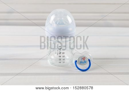 Glass Baby Bottle And Baby Pacifier On White Wooden Background