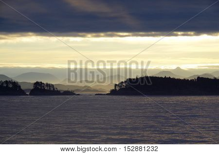 Dark clouds above bright sun in the middle mountains and silhouetted islands with the purple sea below make a dynamic picture of early morning in the Queen Charlotte Strait.