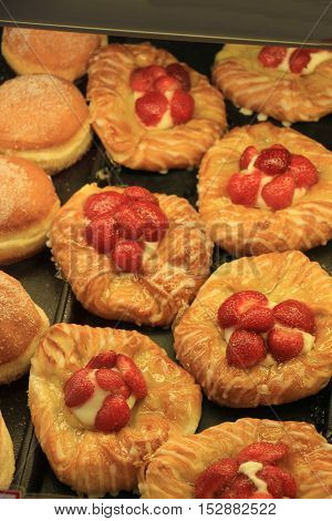 Fresh strawberries on puff pastry displayed in a bakery shop