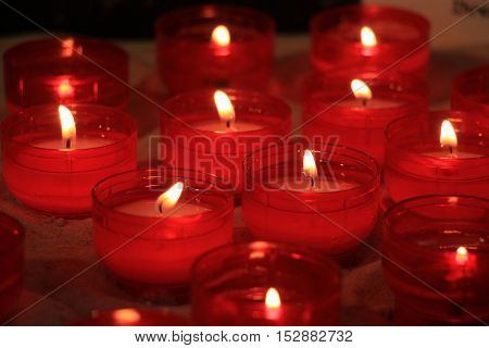 Red votive candles burning in a church