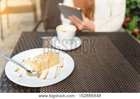 Close up of young woman is sitting in cafeteria and holding tablet. Focus on cup of coffee and piece of cake on table