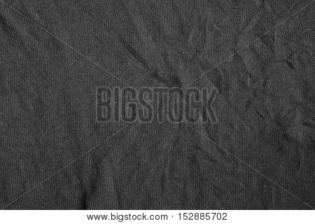 Black fabric background with delicate striped pattern crumpled. Dark fabric texture.