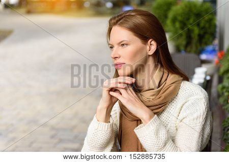 Pensive young woman is relaxing in cafe outdoors