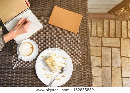 Top view close-up of female hands writing down into notebook. Cup of coffee, cake and tablet on table
