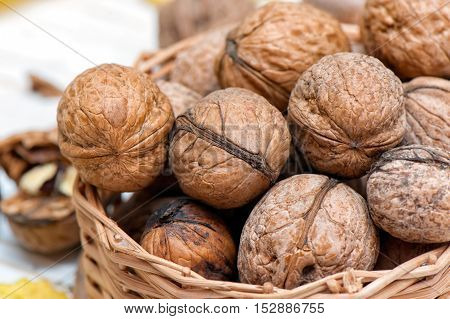 Organic walnuts in small basket on wooden background.