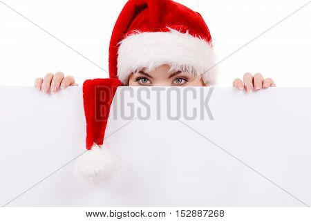Woman holding banner sign peeking over edge of blank empty billboard with copy space for text. Girl in santa claus hat looking funny. Christmas advertisement copyspace.