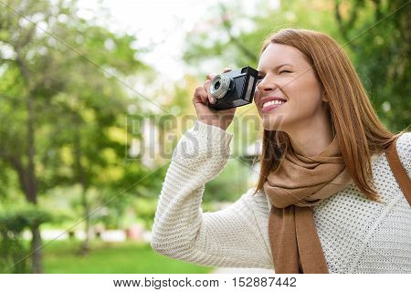 Carefree young woman is taking photos in park. She is looking into camera and laughing