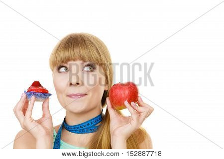 Woman with measuring tape holds in hand cake and apple fruit choosing trying to resist temptation make the right dietary choice. Weight loss diet dilemma gluttony concept. Isolated on white