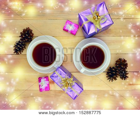 Two cups of hot drink gifts and cones on a wooden table. Top view. Concept. Christmas. Love. Home comfort. holiday atmosphere.