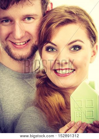 Property ownership family future finances mortgage bank concept. Youthful pair with house model. Young lady with man posing together with home symbol.