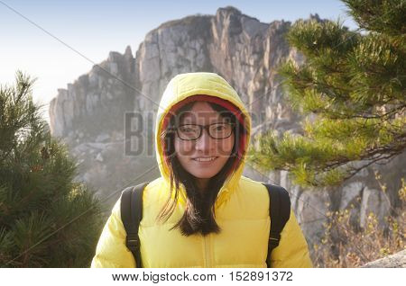 A smiling chinese woman wearing glasses and a yellow winter coat in the early morning on Taishan or Mount Tai in Shandong province China.