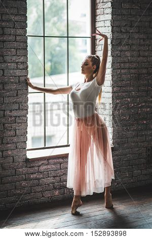 Living her dream. Young and incredibly beautiful ballerina posing and dancing in dance studio against window