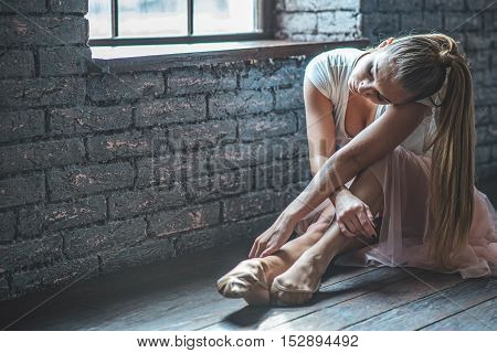 Pleasant tiredness. Photo of pretty ballerina sitting on wooden floor in dance hall, bending one leg at knee