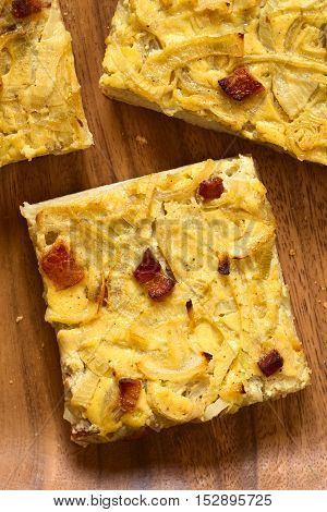 Traditional German Zwiebelkuchen savory onion cake pieces made of onion bacon and cream sauce on yeast dough photographed overhead with natural light (Selective Focus Focus on the top of the cake pieces)