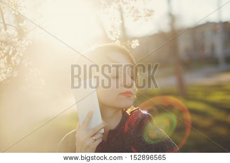 Cute girl with the phone close-up portrait on a background of cherry blossoms and the setting sun. The solar lens flare.