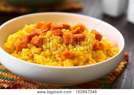 Pumpkin risotto prepared with pumpkin puree roasted pumpkin pieces on top photographed with natural light (Selective Focus Focus in the middle of the image)