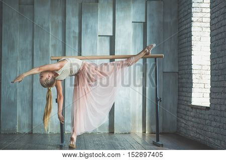 She dances from her heart. Good looking young dancer doing some stretching and warming up in front of window in dance studio