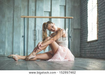 Dancer dream with her feet. Slim good looking girl having dance class and posing at camera with ballet barre in background