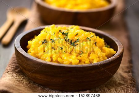 Pumpkin risotto prepared with pumpkin puree and sprinkled with fresh thyme leaves served in wooden bowls photographed with natural light (Selective Focus Focus one third into the risotto)