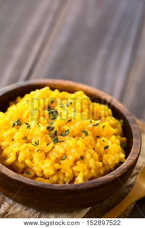 Pumpkin risotto prepared with pumpkin puree and sprinkled with fresh thyme leaves served in wooden bowl photographed with natural light (Selective Focus Focus one third into the risotto)