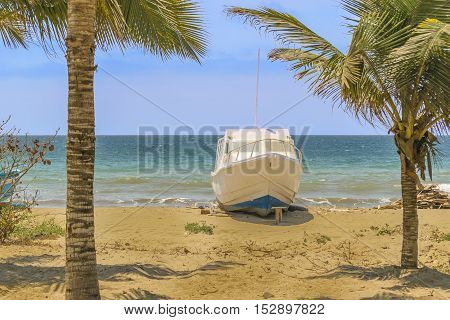 White yatch aground at empty beach in Puerto Lopez town Ecuador South America